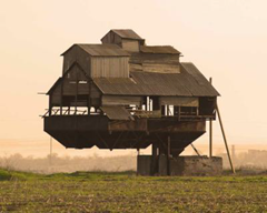 "This ""gravity defying"" home is real. It is supported by a single cantilever.  The owners use it as a barn for storage of mineral fertilizers."